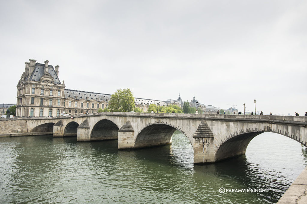 Walking across the Seine River towards the Louvre Museum.