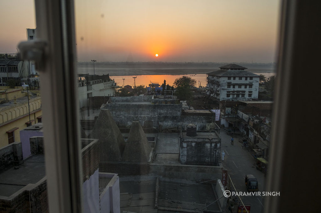 The morning sun rises behind the Ganges in Varanasi
